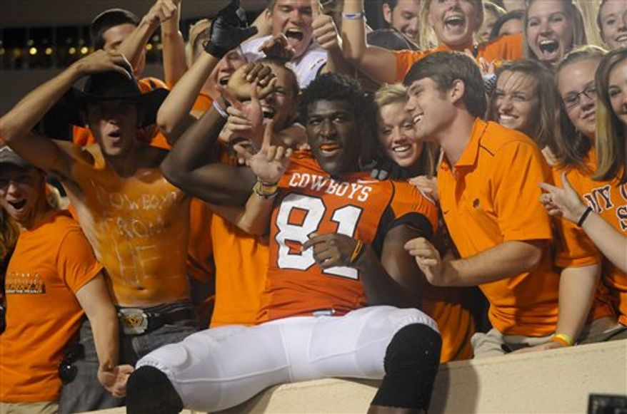FILE - This Sept. 11, 2010, file photo shows Oklahoma State wide receiver Justin Blackmon (81) celebrating with fans following an NCAA college football game in Stillwater, Okla. Blackmon was arrested early Tuesday, Oct. 26, 2010,  on a suburban Dallas highway on a misdemeanor DUI complaint and his status with the Cowboys was unclear headed into the final weeks of the season.  (AP Photo/Brody Schmidt, File)
