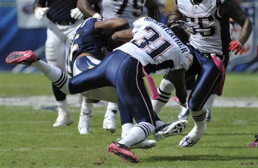 New England Patriots coach Bill Belichick kneels to urge on his defense late in the fourth quarter of the Patriots' 23-20 victory over the San Diego Chargers in an NFL football game Sunday, Oct. 24, 2010, in San Diego. (AP Photo/Lenny Ignelzi)