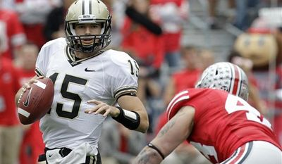 FILE - In this Oct. 23, 2010, file photo, Purdue quarterback Rob Henry looks for a receiver under pressure during the first half an NCAA college football game against Ohio State in Columbus, Ohio. Henry suffered a laceration to his right index finger and is questionable for Saturday's game at Illinois.(AP Photo/Tony Dejak, File)