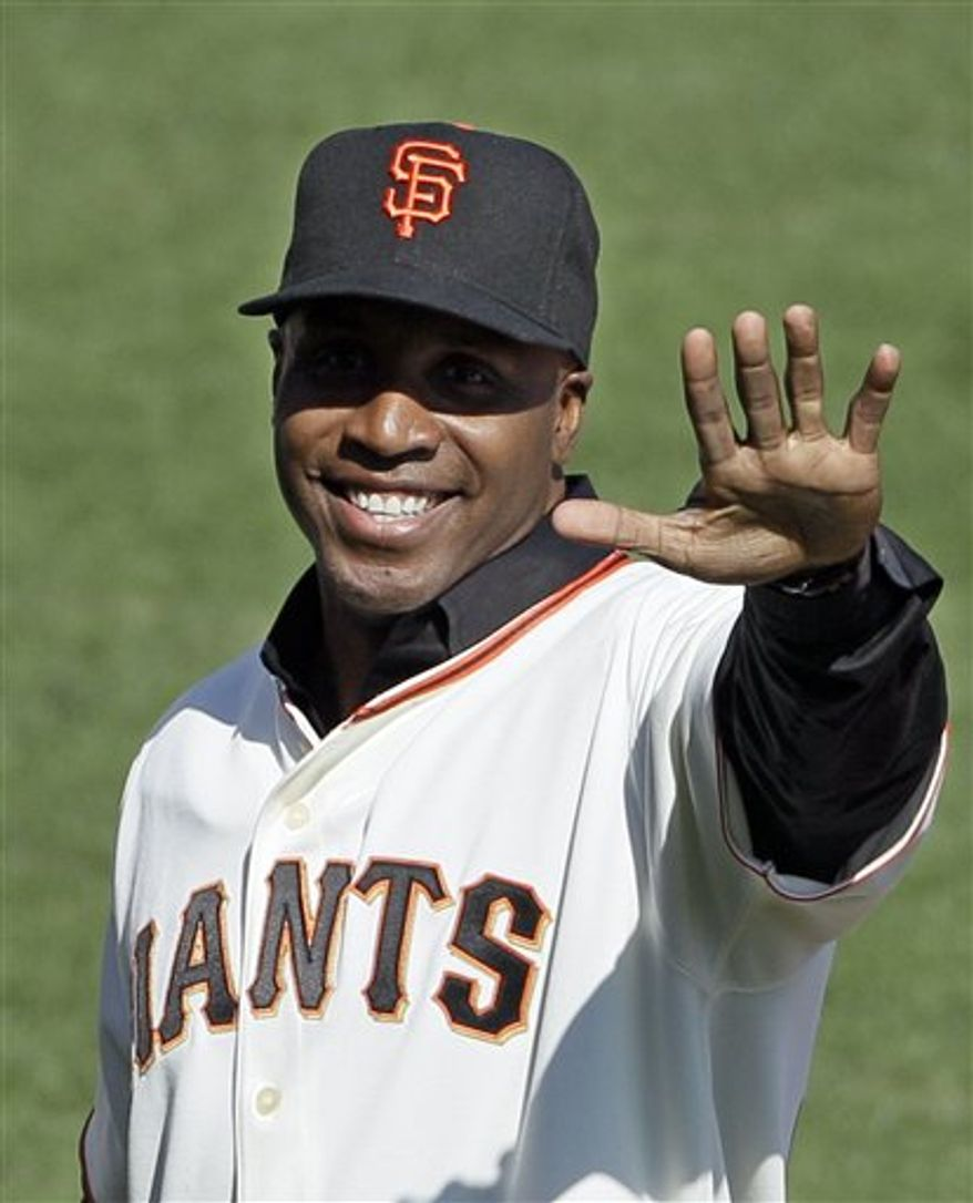 FILE - In this Oct. 19, 2010 file photo, former San Francisco Giants player Barry Bonds acknowledges the crowd before throwing out the ceremonial first pitch before Game 3 of baseball's National League Championship Series against the Philadelphia Phillies in San Francisco. Even as Bonds' perjury trial looms early next year, he has emerged from his estrangement with the team. In recent weeks he has appeared in the broadcast booth of the team's flagship radio station, then to wild applause when he threw out the first ball in Game 3 of the NLCS. (AP Photo/Eric Risberg, File)