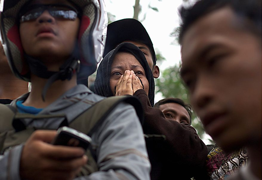 Mourners weep during the funeral of Maridjan,the spiritual guardian of  Mount Merapi, during his funeral in Glagaharjo, Yogyakarta, Indonesia, Thursday, Oct. 28, 2010.  For 33 years, Maridjan spoke to Mount Merapi, appeasing its unpredictable spirits by throwing offerings of rice, clothes and chickens into the volcano's gaping crater. As Merapi began spewing 1,800 degree Fahrenheit (1,000 Celsius) gases and thousands of villagers streamed down the mountain's slopes, Maridjan refused to budge. His rigid body was found Wednesday, prostrate on the ground in the typical Islamic prayer position and caked in heavy white soot. (AP Photo/Gembong Nusantara)