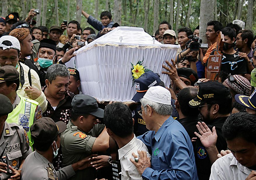 Relatives carry the coffin of Maridjan,the spiritual guardian of  Mount Merapi, during his funeral in Glagaharjo, Yogyakarta, Indonesia, Thursday, Oct. 28, 2010 . For 33 years, Maridjan spoke to Mount Merapi, appeasing its unpredictable spirits by throwing offerings of rice, clothes and chickens into the volcano's gaping crater. As Merapi began spewing 1,800 degree Fahrenheit (1,000 Celsius) gases and thousands of villagers streamed down the mountain's slopes, Maridjan refused to budge. His rigid body was found Wednesday, prostrate on the ground in the typical Islamic prayer position and caked in heavy white soot. (AP Photo/Slamet Riyadi)
