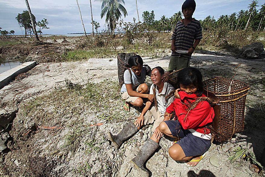 A woman who lost her house and husband in the earthquake-triggered tsunami, weeps with her two daughters on Pagai island, in Mentawai Islands, Indonesia, Thursday, Oct. 28, 2010. (AP Photo/Tundra Laksamana)
