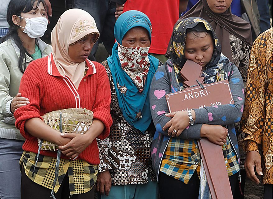 Relatives attend the mass burial of the victims of Mount Merapi eruption  in Umbulharjo, Yogyakarta, Indonesia, Thursday, Oct. 28, 2010. (AP Photo/Irwin Fedriansyah)