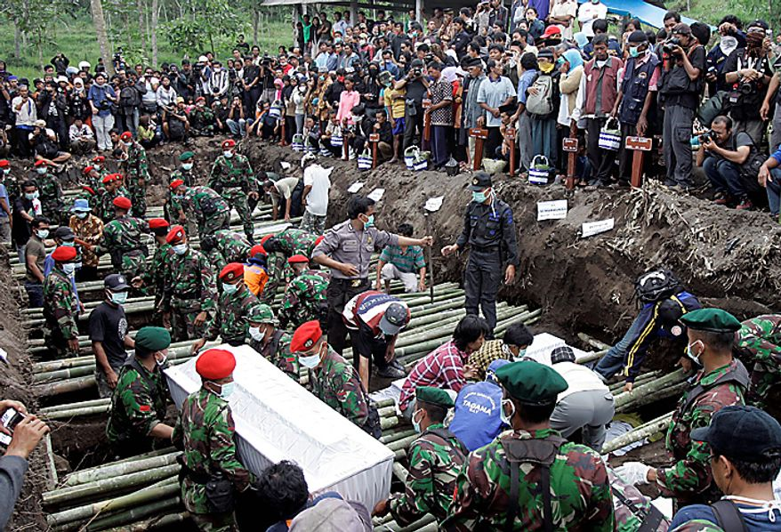 Indonesian soldiers carry the coffin of a victim of Mount Merapi eruption during a mass burial in Umbulharjo, Yogyakarta, Indonesia, Thursday, Oct. 28, 2010. (AP Photo/Irwin Fedriansyah)