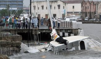 Bystanders look at a sunken boat after then-Tropical Storm Tomas hit Bridgetown, Barbados, on Saturday, Oct. 30, 2010. Tomas, now a Category 1 hurricane, is expected to affect Haiti later this week. (AP Photo/Chris Brandis)