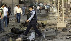 An Iraqi policeman stands guard at the scene of a car-bomb attack in front of a Syrian Catholic church in Baghdad on Monday, Nov. 1, 2010. Islamic militants held about 120 Iraqi Christians hostage for nearly four hours in the church on Sunday before security forces stormed the building and freed them, ending a standoff that left dozens of people dead, U.S. and Iraqi officials said. (AP Photo/Khalid Mohammed)