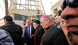 Iraqi Christian lawmaker, Younadem Kana, center left, Iraq's top Catholic prelate, Chaldean Cardinal Emmanuel III Delly, center, and Bishop Shlimone Wardoni, center right, are seen outside Our Lady of Deliverance church the morning after its congregation was taken hostage in Baghdad, Iraq, Monday Nov. 1, 2010. Iraqi security forces stormed a Baghdad church where militants had taken an entire congregation hostage for four hours, leaving dozens of people dead, including a priest, Iraqi officials said Monday.(AP Photo/Hadi Mizban)