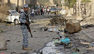 **FILE** An Iraqi policeman stands guard at the scene of a car bomb attack in front of a Syrian Catholic Church in Baghdad on Nov. 1, 2010. (Associated Press)