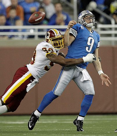 Washington Redskins linebacker Andre Carter (99) hits Detroit Lions quarterback Matthew Stafford (9), jarring the ball loose, during the first quarter of their NFL football game in Detroit, Sunday, Oct. 31, 2010. (AP Photo/Paul Sancya)