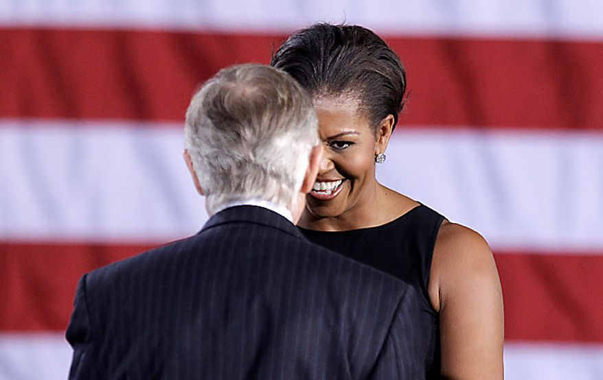 First lady Michelle Obama greets Senate Majorty Harry Reid of Nev. during a rally, Monday, Nov. 1, 2010, in Las Vegas. (AP Photo/Julie Jacobson)