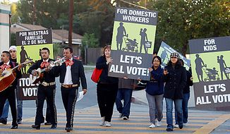 "Members of the mariachi band ""Los Munecos,"" along with volunteers from the Coalition for Humane Immigrant Rights of Los Angeles (CHIRLA) urge immigrant voters to vote early in the California election in Los Angeles on Tuesday, Oct. 2, 2010. (AP Photo/Damian Dovarganes/File)"