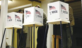 Three men cast their ballots on election day in the basement of Zion Lutheran Church Tuesday, Nov. 2, 2010, in Waterloo, Iowa. (AP Photo/The Waterloo Courier, Matthew Putney)