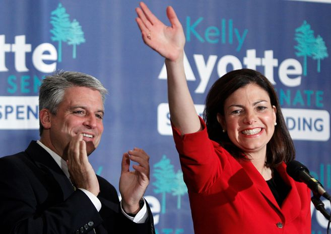 New Hampshire Sen.-elect Kelly Ayotte, a Republican, with husband Joe Daley by her side, celebrates winning the Senate race in Concord, N.H., on Tu
