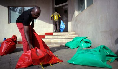 Ivory Coast Electoral Commission workers on Wednesday carry sealed bags containing votes to be tallied by the EC in Abidjan. With about 35 percent of votes cast, President Laurent Gbagbo had a three-point lead over main opponent Alassane Ouattara. (Associated Press)