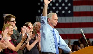 Wisconsin Republican Ron Johnson, a political novice, celebrates his victory over veteran Democratic Sen. Russ Feingold Tuesday night in Oshkosh, Wis., with family and supporters. (Associated Press)