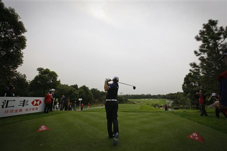Phil Mickelson of Britain, left, Tiger Woods of the U.S., second from left, Lee Westwood of Britain, second from right, and Martin Kaymer of Germany, right, strike a pose with swords as they perform the Chinese martial art of taichi on stage against the Pudong Financial District during a photo call in Shanghai, China Tuesday, Nov. 2, 2010. (AP Photo/Andy Wong)
