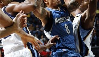Minnesota Timberwolves forward Michael Beasley (8) drives to the basket defended by Memphis Grizzlies forward Rudy Gay, left, and Darrell Arthur, right, in the first half of an NBA basketball game Saturday, Oct. 30, 2010, in Memphis, Tenn. (AP Photo/Nikki Boertman)