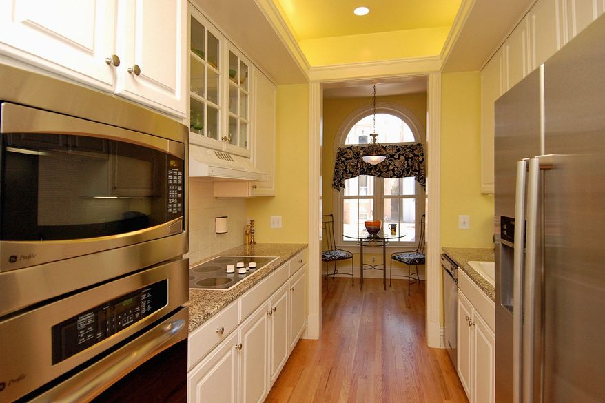 The kitchen has a tray ceiling, a hardwood floor, granite counters and stainless steel appliances.