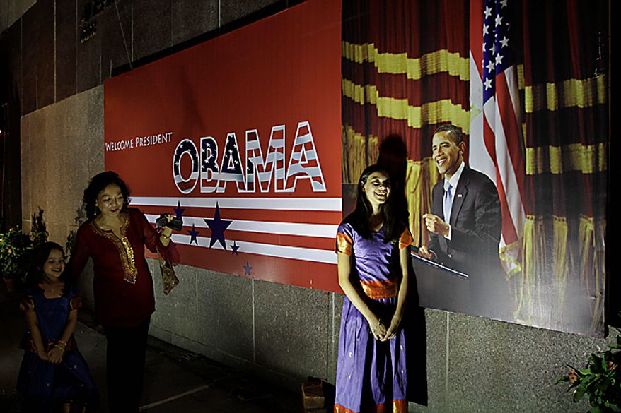 A woman makes her daughters pose for a photograph besides a poster of U.S. President Barack Obama in Calcutta, India, Thursday, Nov. 4, 2010. Obama is scheduled to visit India Nov. 6-9. (AP Photo/Bikas Das)