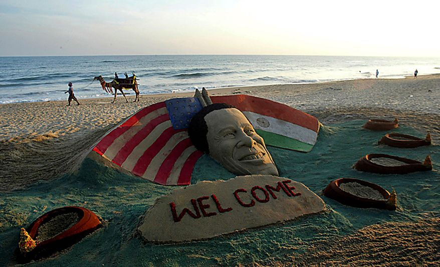 A man walks with a camel past a sand sculpture depicting President Barack Obama ahead of Obama's arrival to the country, in Puri, India, Thursday, Nov. 4, 2010. President Obama is expected to visit India from Nov. 6-9. (AP Photo/Biswaranjan Rout)