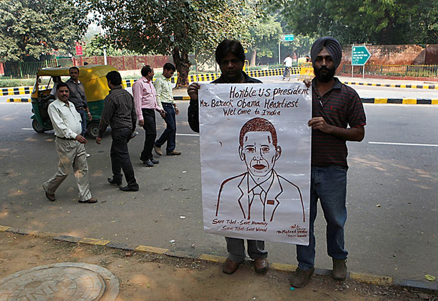 Mahesh Gupta, center left, holds a portrait of U.S. President Barack Obama which he claims to have made from his blood as an act to welcome him, ahead of his visit to India, in New Delhi, India, Thursday, Nov. 4, 2010. President Obama is expected to visit India from Nov. 6-9. (AP Photo/Manish Swarup)