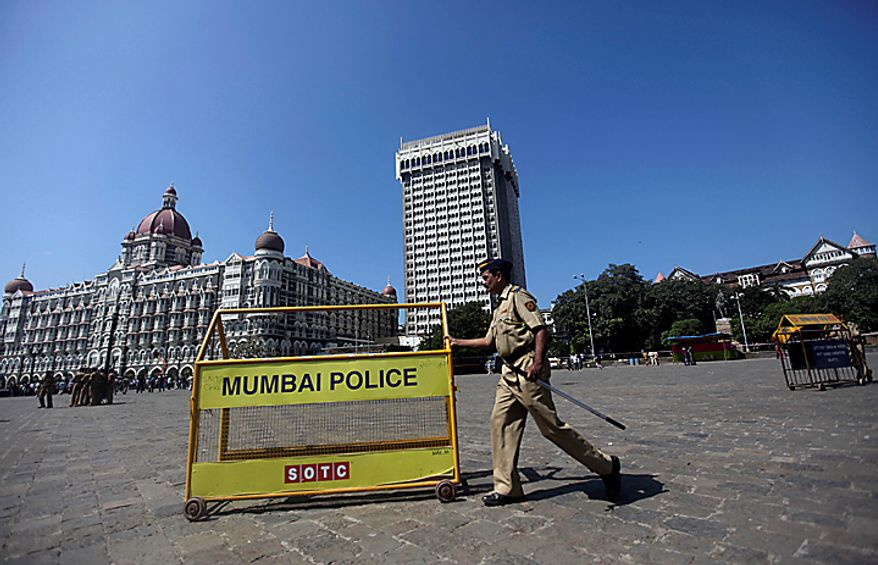 An Indian policeman pushes a barricade outside the Taj Mahal hotel in Mumbai, India, Thursday, Nov. 4, 2010. President Barack Obama is scheduled to stay at the Taj on Nov. 6. The 107-year-old hotel reopened for business in August, nearly two years after it was attacked by terrorists in 2008. (AP Photo/Rafiq Maqbool)