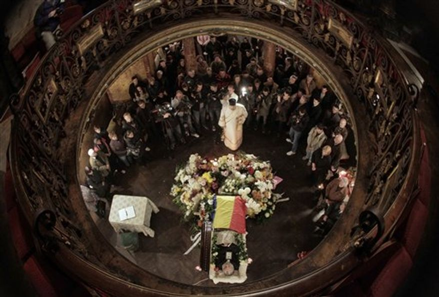 An Orthodox priest sings as mourners stand around the coffin of Romanian poet Adrian Paunescu at the Writers Union in Bucharest, Romania, Friday, Nov. 5, 2010. Paunescu, Romania's most famous poet who praised ex dictator Nicolae Ceausescu, yet whose sentimental verse struck a chord with many Romanians has died. He was 67.(AP Photo/Vadim Ghirda)