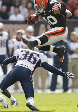 Cleveland Browns running back Peyton Hillis, top, leaps over New England Patriots safety Josh Barrett (36) on a first-quarter run in an NFL football game Sunday, Nov. 7, 2010, in Cleveland. (AP Photo/Tony Dejak)