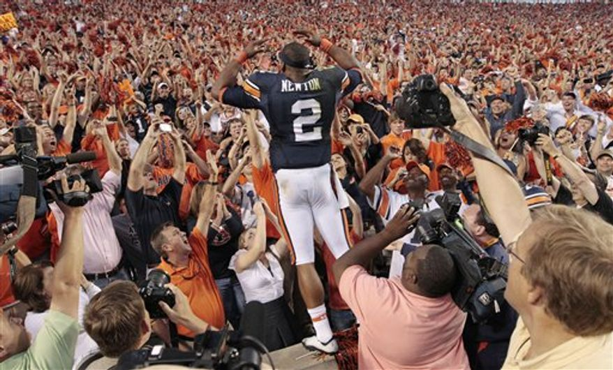 FILE - This oct. 23, 2010, file photo shows Auburn quarterback Cameron Newton celebrating with fans after a 24-17 win over LSU in an NCAA college football game at Jordan-Hare Stadium in Auburn, Ala. A man who said he represented Auburn quarterback and Heisman hopeful Cameron Newton during his recruitment out of junior college last year asked for payment to secure his commitment to Mississippi State, according to former MSU player John Bond. (AP Photo/Dave Martin, File)