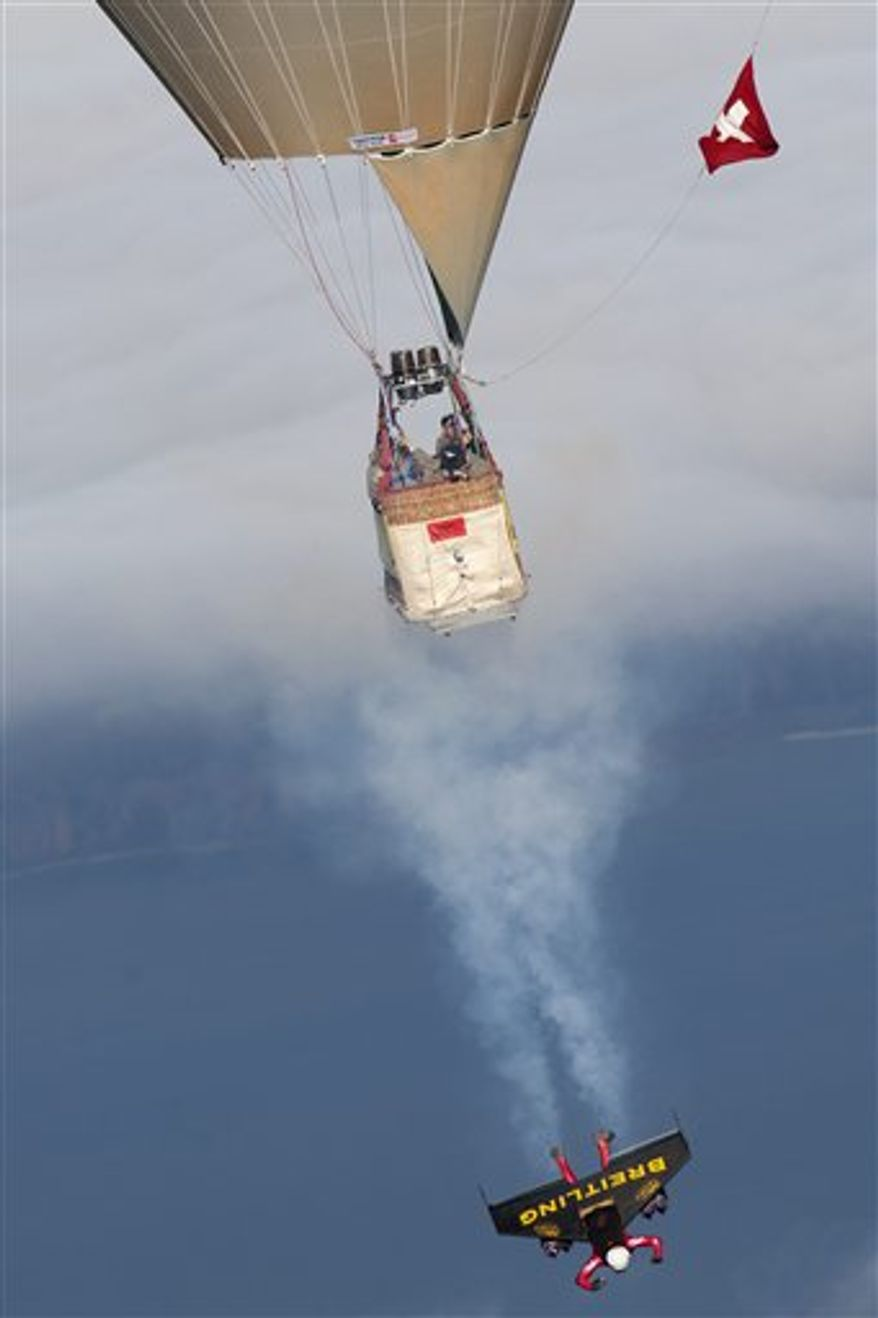 Swiss pilot Yves Rossy, the first man in the world to fly under a jet-fitted wing, stands on a platform of a hot air balloon in Bercher, western Switzerland, Friday, Nov. 5, 2010. Rossy has completed two aerial loops using a custom-made jet-propelled wingsuit after he jumped from the balloon.  (AP Photo/Keystone, pool, Laurent Gillieron)