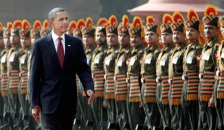 "RED CARPET: President Obama reviews an Indian honor guard after his arrival Monday at the presidential palace in New Delhi. Mr. Obama pledged U.S. assistance in helping to resolve the long-running conflict over the disputed territory of Kashmir, but said the U.S. ""cannot impose a solution."" (Associated Press)"