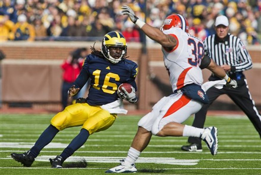 Michigan running back Vincent Smith (2) gets a hand from quarterback Denard Robinson (16) after a Michigan touchdown in the second overtime of an NCAA college football game with Illinois, Saturday, Nov. 6, 2010, in Ann Arbor. Michigan won 67-65 in triple overtime. (AP Photo/Tony Ding)