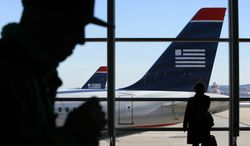 **FILE** Passengers walk past US Airways planes at Ronald Reagan Washington National Airport in suburban Washington on Dec. 27, 2009. (Associated Press)