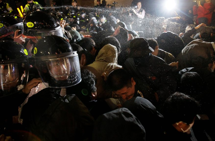 Pepper spray is fired at protesters as they clash with riot police during a protest denouncing the upcoming Group of 20 summit on Sunday in Seoul. Twenty world leaders will come together in Seoul on Nov. 11 and 12 to discuss the state of the global economy. (Associated Press)