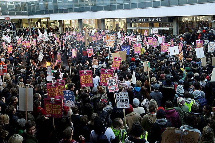 Thousands of protesting students gather outside the headquarters of Britain's Conservative Party in London, Wednesday Nav. 10, 2010, in a demonstration against plans to increase tuition fees and cut university funding. Organizers claimed that 50,000 students, lecturers and supporters were demonstrating against plans to raise the cost of studying to 9,000 pounds ($14,000) a year - three times the current rate.(AP Photo/Sang Tan)