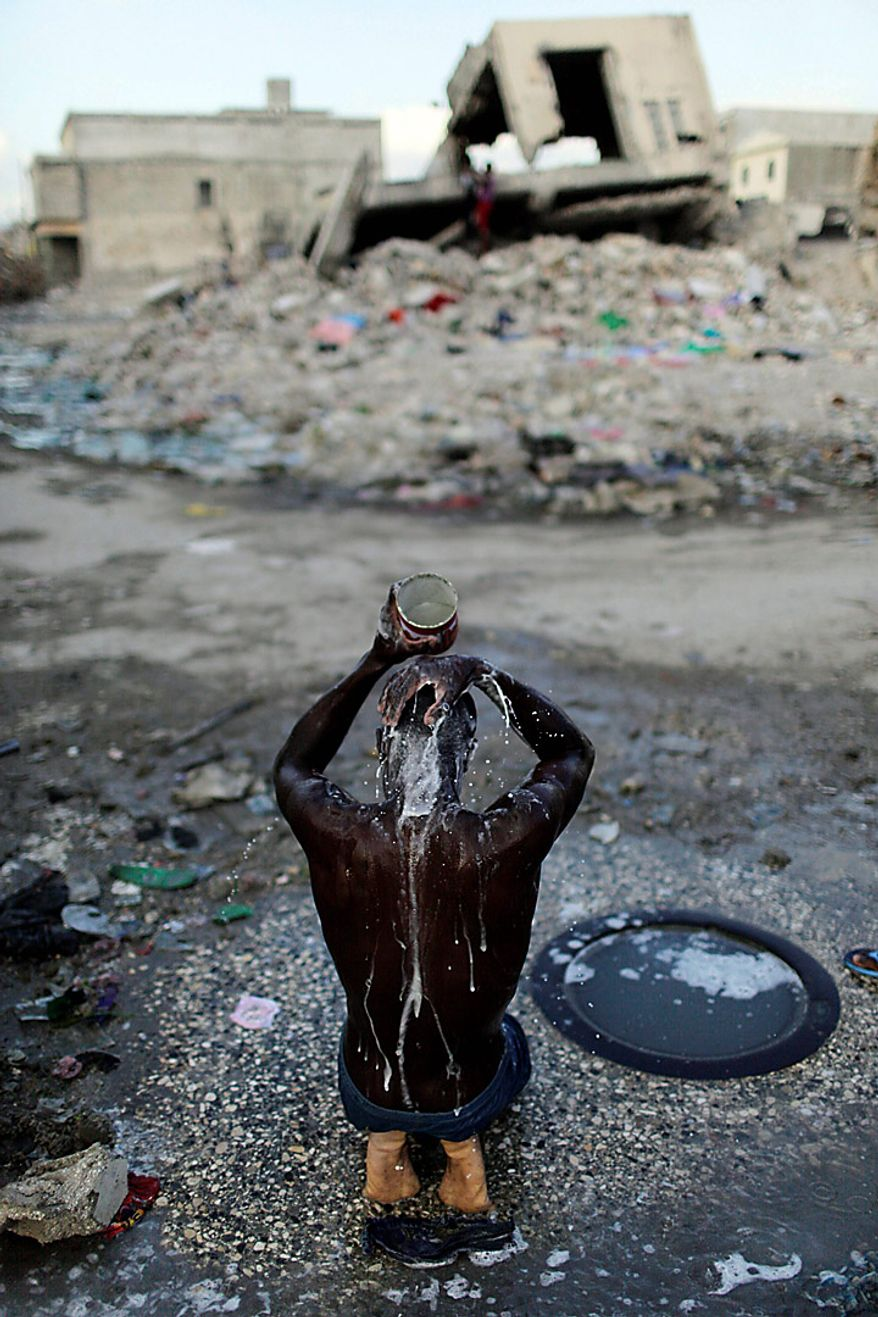 A man bathes with water collected from a puddle in a street of Port-au-Prince, Haiti, Monday Nov. 8, 2010. (AP Photo/Ariana Cubillos)