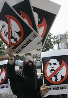 An Indonesian Muslim woman holds posters during a protest against the visit of President Obama in front of the U.S. Embassy in Jakarta, Indonesia, on Tuesday. In an address at the Univeristy of Indonesia, Mr. Obama said that international problems only can be solved through partnership. (Associated Press)