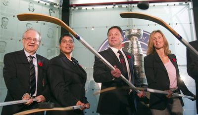 Hockey Hall of Fame inductees from left, Jim Devellano, Angela James, Dino Ciccarelli and Cammi Granato flip pucks off sticks after being presented with their rings at the Hall in Toronto on Monday, Nov. 8, 2010. (AP Photo/The Canadian Press, Frank Gunn)