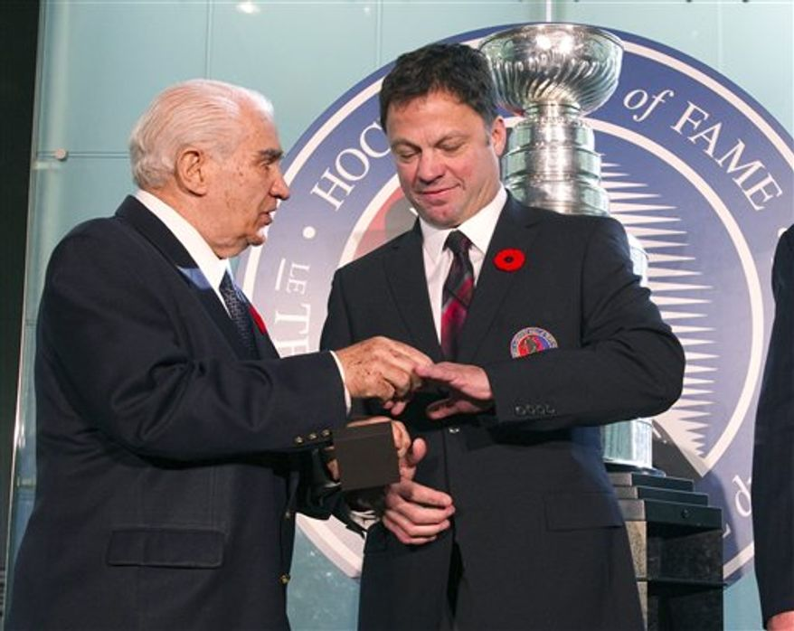 Hockey Hall of Fame inductee Dino Ciccarelli, right, is given his ring by Hall Co-Chairman Jim Gregory at the Hall in Toronto on Monday Nov. 8, 2010. (AP Photo/The Canadian Press, Frank Gunn)