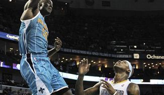 FILE - This Oct. 29, 2010, file photo shows New Orleans Hornets center Emeka Okafor (50)  dunking over Denver Nuggets power forward Al Harrington (7) in the second half of an NBA basketball game in New Orleans. Coming off perhaps his worst season, Emeka Okafor is now primed for one of his best with the resurgent Hornets.  (AP Photo/Gerald Herbert, File)