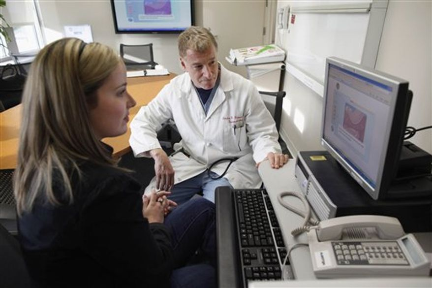 Kristen Miller, a colonoscopy patient, views with Dr. Stephen Hanauer, gastroenterology chief at the University of Chicago Medical Center in Chicago, an interactive computer program describing benefits and risks of the procedure in October 2010. (AP Photo/Brian Kersey)