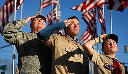 Chief Master Sgt. Bill Ross, a 35-year Air Force veteran, left, and Boy Scouts 19-year-old Tyler Pollock, and 12-year-old Liam Gallagher salute in honor of war veterans, Thursday, Nov. 11, 2010, in Freeport, Maine.  The boy scouts and other volunteers raised 50 casket flags donated by the families of Freeport veterans. (AP Photo/Robert F. Bukaty)