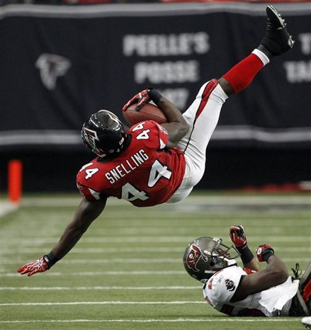 Tampa Bay Buccaneers tight end Erik Lorig, left, tries to hold onto the ball as Atlanta Falcons defensive end John Abraham, right,  breaks up the catch during the third quarter of an NFL football game, Sunday, Nov. 7, 2010, in Atlanta. (AP Photo/David Goldman)