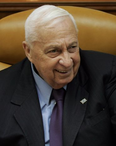 ** FILE ** Then-Israeli Prime Minister Ariel Sharon smiles as he talks to journalists on Sunday, Dec. 18, 2005, before the weekly Cabinet meeting in Jerusalem. (AP Photo/ Emilio Morenatti)