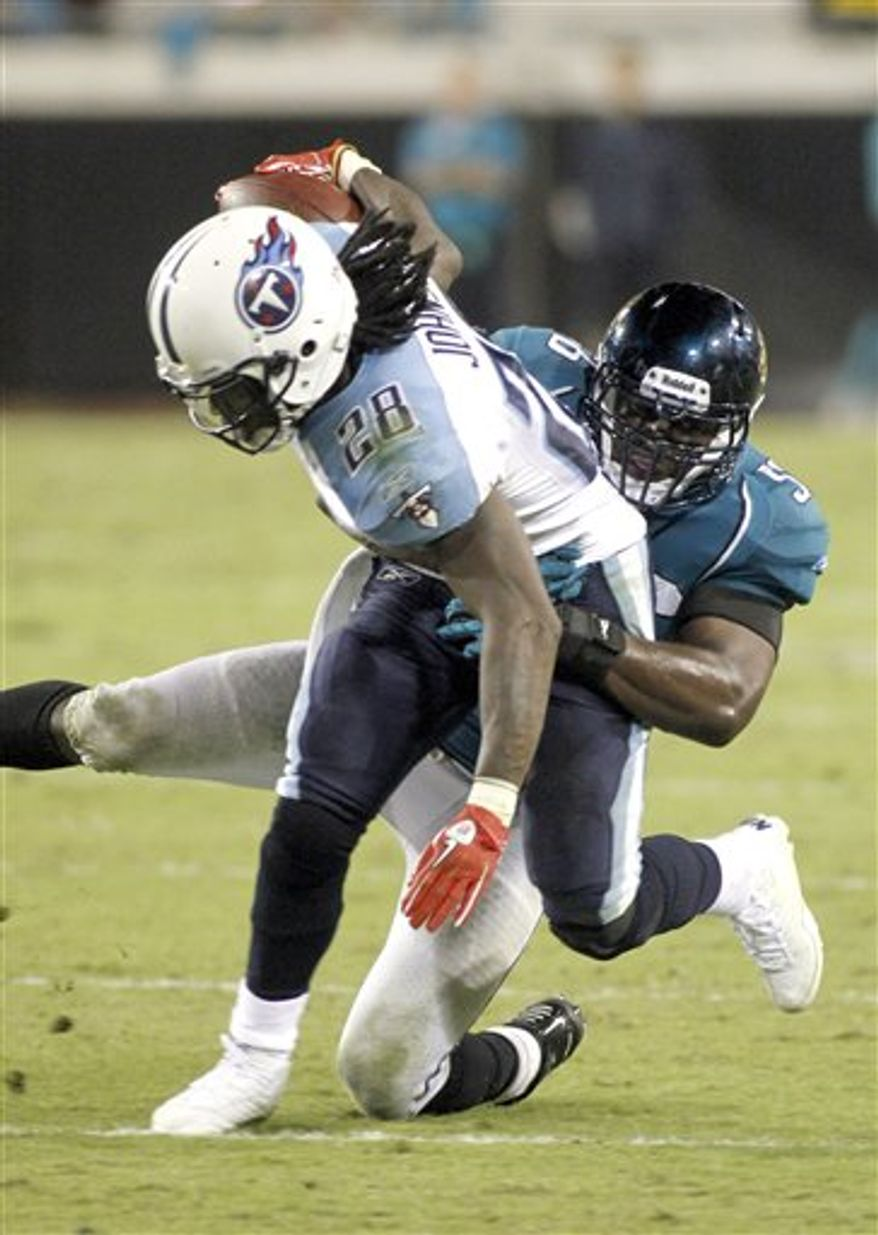 FILE - This Oct. 18, 2010, file photo shows Tennessee Titans running back Chris Johnson (28) being tackled by Jacksonville Jaguars linebacker Justin Durant (56) during an NFL football game in Jacksonville, Fla. CJ and the Titans are struggling in the run game as they prepare to play Miami. (AP Photo/Reinhold Matay, File)