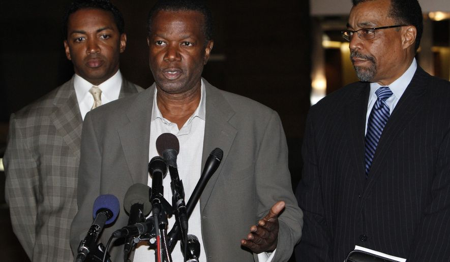 Prince George's County Executive Jack Johnson, 61, center, speaks to the media with his lawyers Brian McDaniel, left, and Billy Martin, outside U.S. District Court, Friday, Nov. 12, 2010, in Greenbelt, Md. Johnson and his wife Leslie were arrested by federal law enforcement agents and charged with witness tampering and destruction of records. (AP Photo/Jacquelyn Martin)