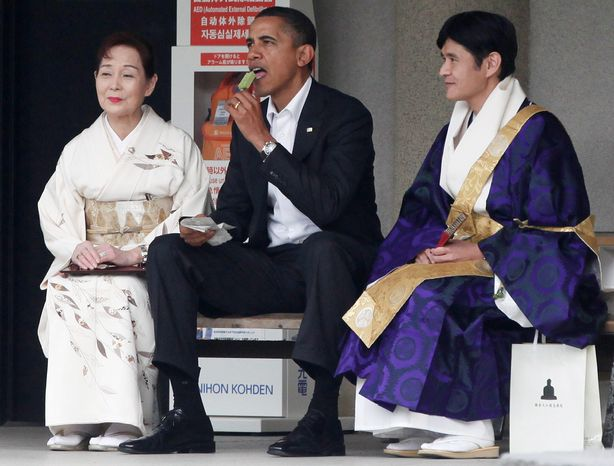 ASSOCIATED PRESS President Obama eats green tea ice cream on Sunday as he visits the Great Buddha of Kamakura with Michiko Sato, temple director, and Takao Sato, the 15th chief monk of the temple, at Kotokuin Temple in Kamakura, Japan.