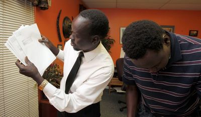 Ajak Dau Akech (left) and Kuol Awan, executive director of the Arizona Lost Boys Center - both are Sudanese war orphans and part of the group known as the Lost Boys of Sudan - look through refugee identification document packages to be mailed to Lost Boys around the world.