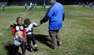 """Curtis """"Coach Peedy"""" Monroe leads practice of the Benning Terrace Pop Warner football team in Washington. The coach tried to save Chicquelo Abney from the streets by keeping him involved in football. His Pop Warner football coaches recall that he took his performance on the field - and his appearance - seriously. (J.M. EDDINS JR./THE WASHINGTON TIMES/File)"""